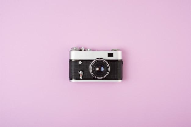 Retro film camera on a pink background.