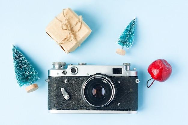 Retro film photo camera, fir trees, apple and cones. christmas concept