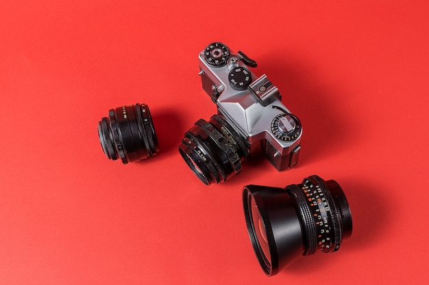 Retro film photo camera and lenses isolated on red background.