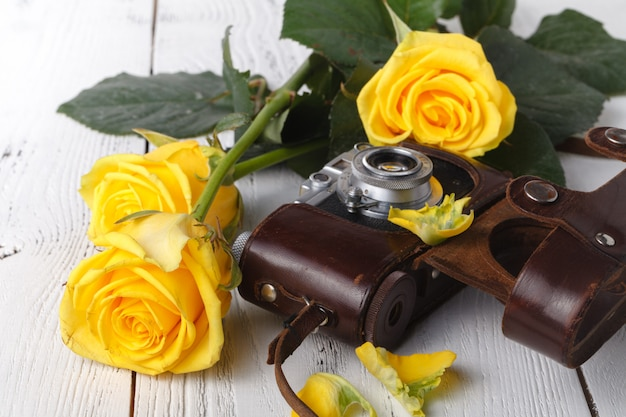 Retro film photocamera with yellow roses