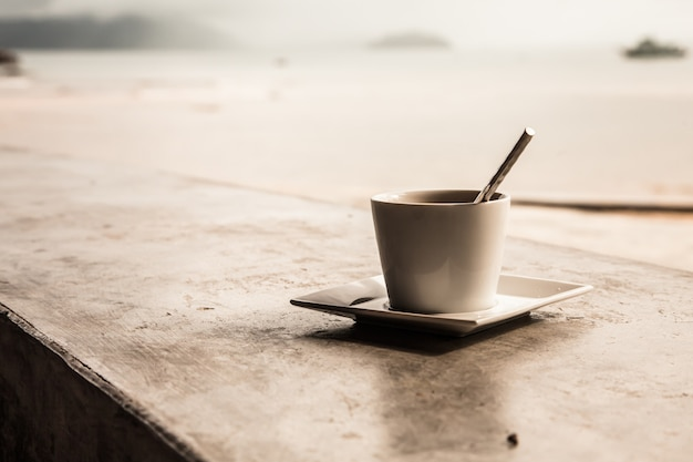 Retro filter of hot coffee cup and beach