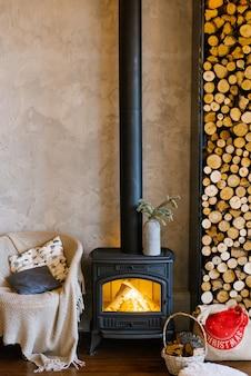 カントリーハウスのレトロな暖炉、木とアームチェア、毛布と枕