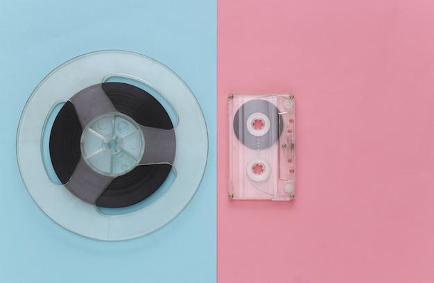 レトロなフラットレイ。ピンクブルーパステルカラーのオーディオ磁気テープリールとオーディオカセット