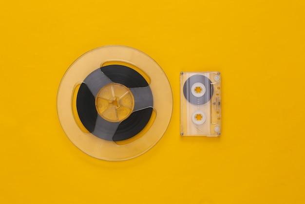 レトロなフラットレイ。黄色のオーディオ磁気テープリールとオーディオカセット