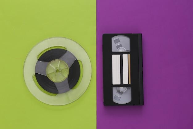 レトロなフラットレイ。紫緑色のオーディオ磁気テープリールとビデオカセット