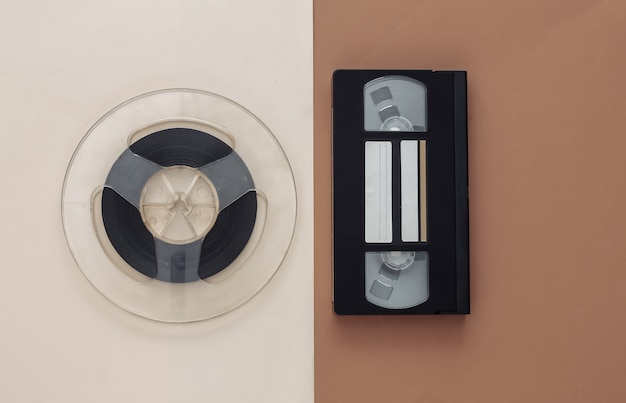 レトロなフラットレイ。ブラウンベージュのオーディオ磁気テープリールとビデオカセット