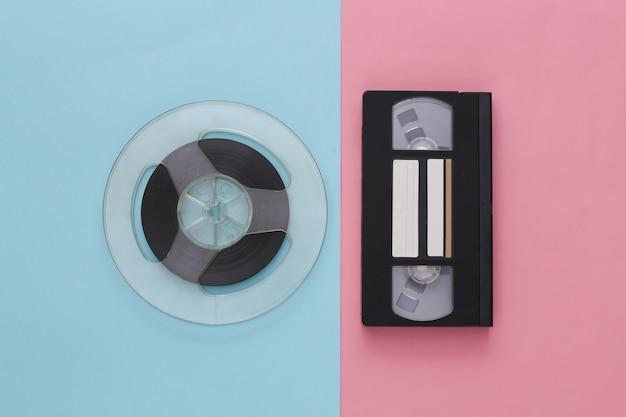レトロなフラットレイ。ピンクブルーパステルカラーのオーディオ磁気テープリールとビデオカセット