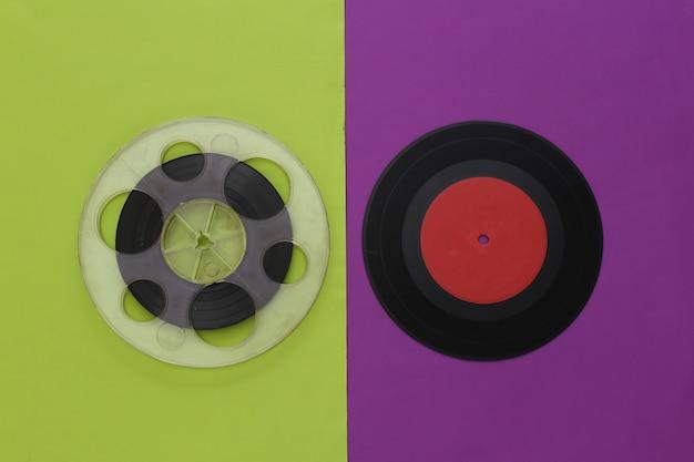 レトロなフラットレイ。紫緑色のオーディオ磁気テープリールとビニールプレート