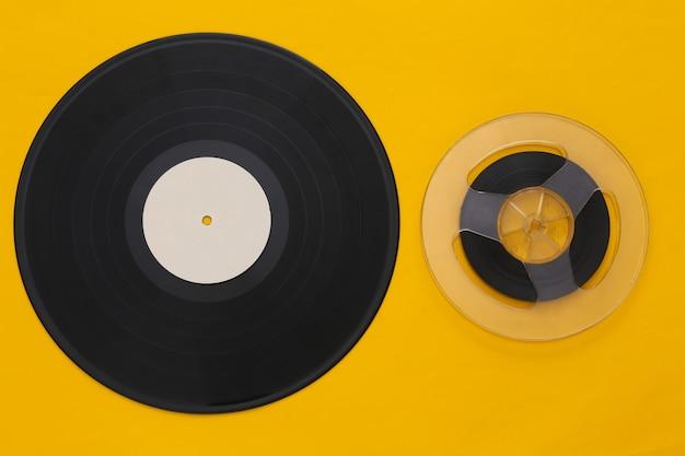 레트로 플랫 누워. 노란색에 오디오 자기 테이프 릴 및 비닐 플레이트