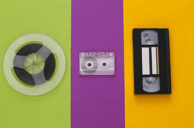 レトロなフラットレイ。色付きのテーブルにオーディオ磁気テープリール、オーディオおよびビデオカセット