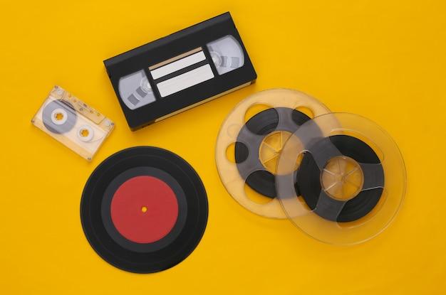 레트로 플랫 누워. 오디오 자기 테이프 릴, 오디오 및 비디오 카세트, 노란색 비닐 플레이트