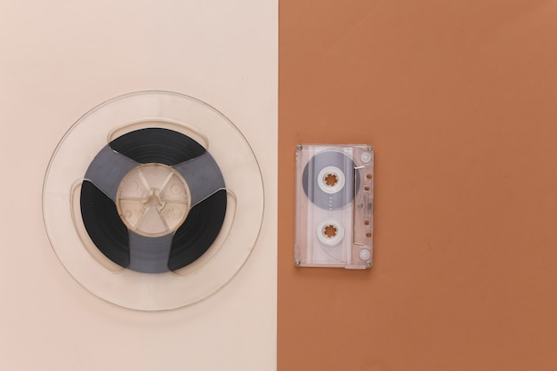 Retro flat lay. audio magnetic tape reel and audio cassette on brown beige
