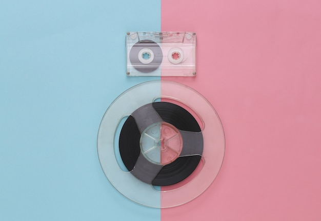 Retro flat lay. audio magnetic tape reel and audio cassette on pink blue pastel