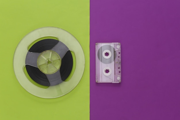 Retro flat lay. audio magnetic tape reel and audio cassette on a purple green