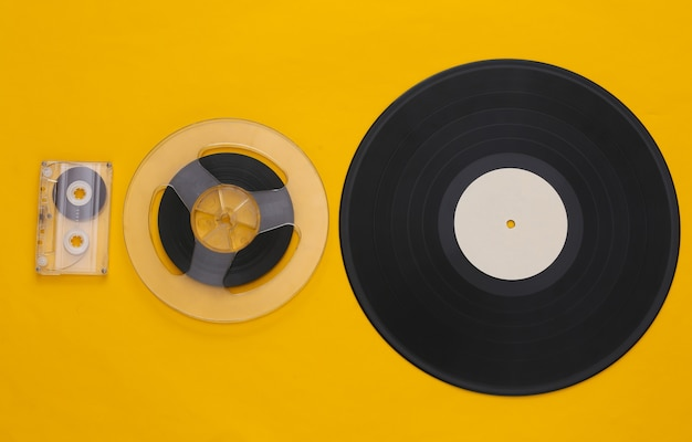 Retro flat lay. audio magnetic tape reel, audio cassette and vinyl plate on yellow