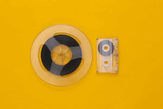 Retro flat lay. audio magnetic tape reel and audio cassette on yellow