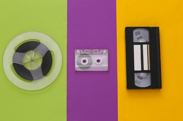 Retro flat lay. audio magnetic tape reel, audio and video cassette on colored table