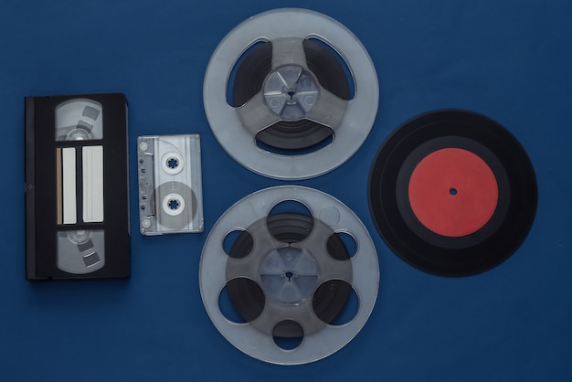 Retro flat lay. audio magnetic tape reel, audio and video cassette, vinyl plate on classic blue