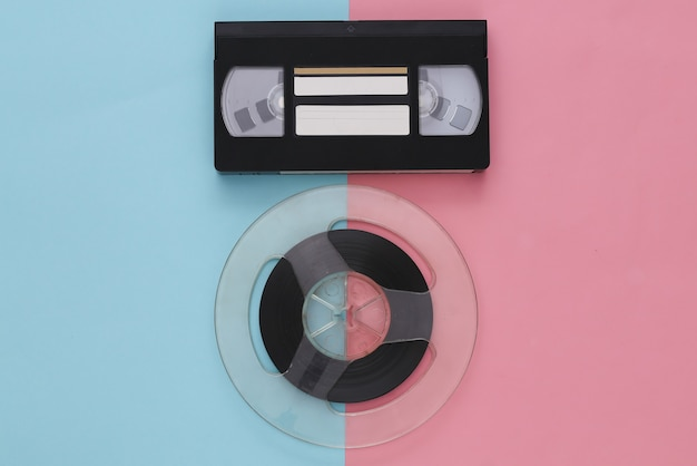 Retro flat lay. audio magnetic tape reel and video cassette on pink blue pastel