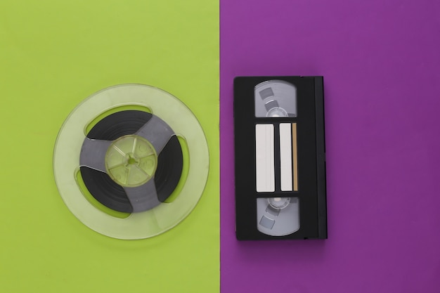 Retro flat lay. audio magnetic tape reel and video cassette on a purple green