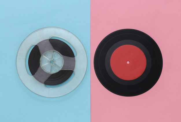 Retro flat lay. audio magnetic tape reel and vinyl plate on pink blue pastel