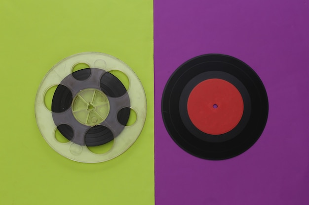 Retro flat lay. audio magnetic tape reel and vinyl plate on a purple green