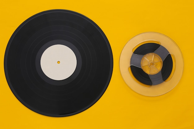 Retro flat lay. audio magnetic tape reel and vinyl plate on yellow