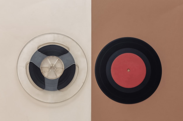 Retro flat lay. audio magnetic tape reel and vinyl record on brown beige