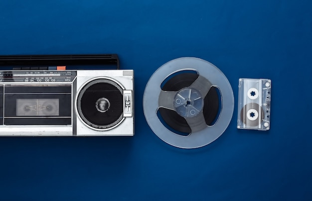 Retro flat lay. retro portable stereo cassette recorder and audio magnetic tape reel, audio cassette on classic blue