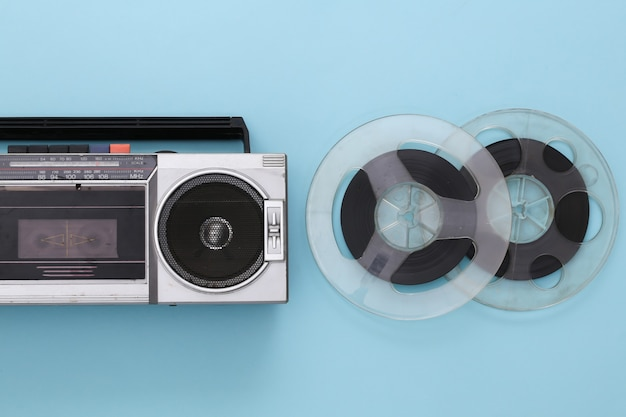 Retro flat lay. retro portable stereo cassette recorder and audio magnetic tape reel on blue pastel