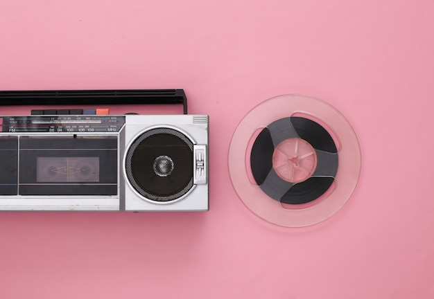 Retro flat lay. retro portable stereo cassette recorder and audio magnetic tape reel on pink