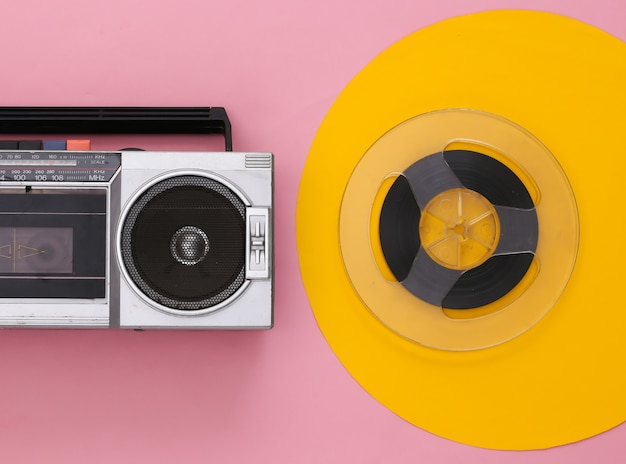 Retro flat lay. retro portable stereo cassette recorder and audio magnetic tape reel on yellow pink
