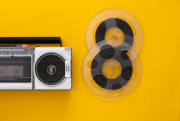Retro flat lay. retro portable stereo cassette recorder and audio magnetic tape reel on yellow