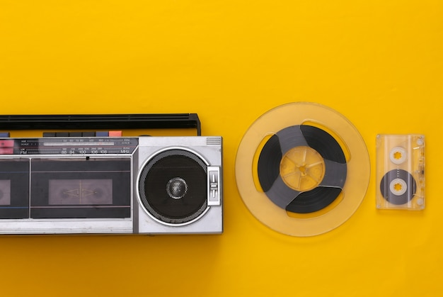 Retro flat lay. retro portable stereo cassette recorder, cassette and audio magnetic tape reel on yellow