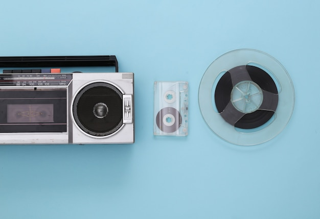 Retro flat lay. retro portable stereo recorder, cassette and audio magnetic tape reel on blue pastel