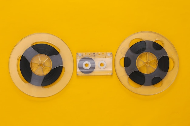 Retro flat lay. two audio magnetic tape reel and audio cassette on yellow