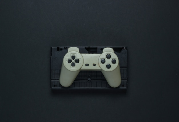 Retro gamepad and video cassette on a black background. top view