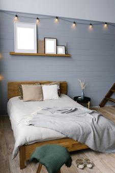 집에 있는 회색 침실 방의 벽에 백열 램프의 복고풍 화환. 더블 침대와 세련된 블랙 나이트 스탠드가 있는 침실의 스칸디나비아 인테리어