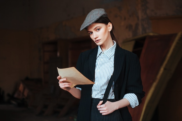 Retro girl in a cap reads a letter