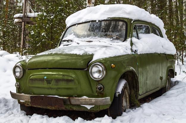 冬の森に立つレトロなグリーン車
