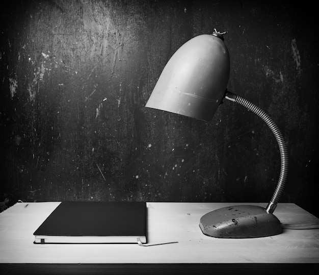 Retro green desk lamp on wooden table, bw photo