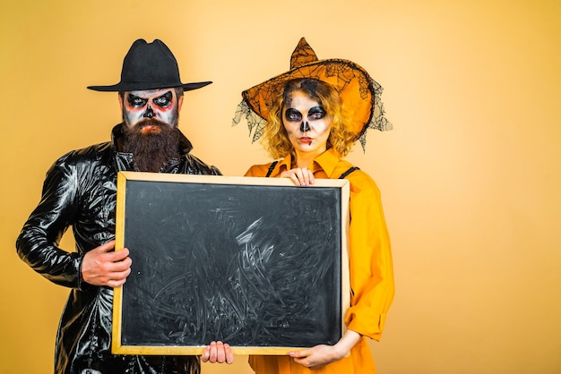 Retro halloween couple romancing beautiful surprised woman in witch hat and costume  showing products