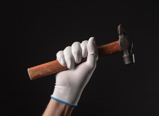 흰색 건물 장갑에 남성 손에 복고풍 망치 도구는 검은 배경 위에 닫습니다.