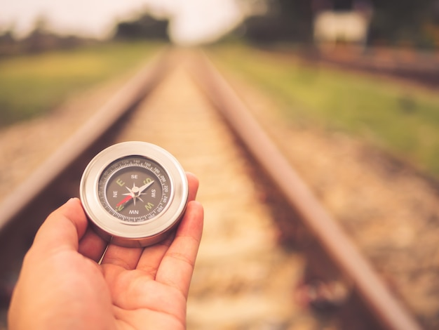 Retro hand holding compass on railway background with copy space on top.