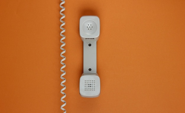 Retro handset phone with cable on a brown