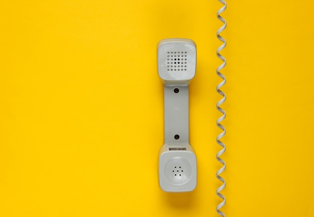 Retro handset phone with cable on yellow
