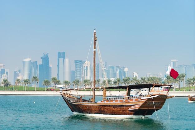 ドーハのモダンなスカイラインと表面の緑のヤシのぼやけたパノラマビューとレトロな歴史的なボート