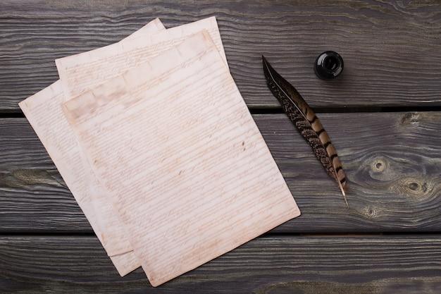 レトロな歴史的な執筆の概念。羽ペンとインク壺。暗い机の背景。