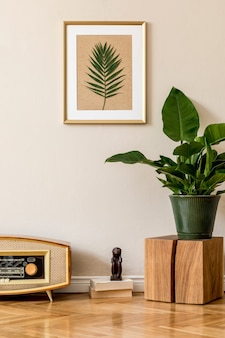 Retro interior design of living room with plants in green pot, vintage radio and gold picture frame on the beige wall. minimalistic concept of home decor. minimalistic concept..