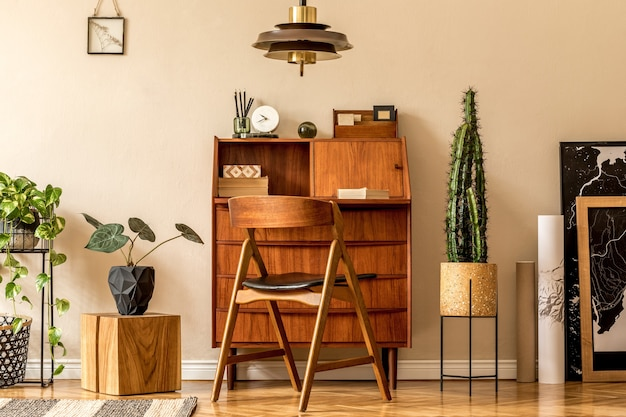 Retro interior design of living room with wooden vintage bureau, design chair, plants, cacti, maps, brown pendant lamp and elegant personal accessories